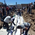 Syrians attend to bodies for a mass funeral